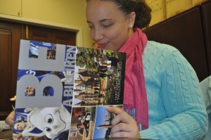 "Senior SLU student ambassador Briana Wright prepares an information pamphlet for prospective SLU students. The ""Be a Billiken"" motto exemplifies SLU's Billiken pride"